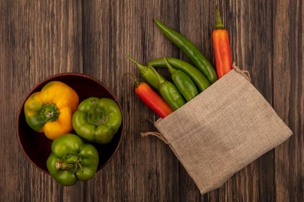木製の壁のボウルにピーマンと黄麻布の袋に新鮮な唐辛子の上面図