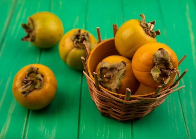 緑の木製テーブルの上のバケツに新鮮な柿の果実の上面図