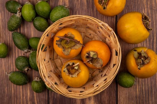 木製の壁に隔離されたフェイジョアとバケツの新鮮な柿の果実の上面図