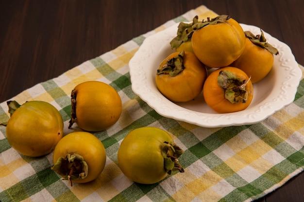 木製のテーブルの上のチェックされた布で分離された柿の果実と白いボウルに新鮮な柿の果実の上面図