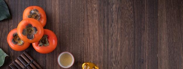 中国の旧正月の木製テーブルの背景に新鮮な柿の上面図