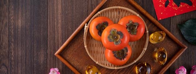 중국 음력 새 해 나무 테이블 배경에 신선한 감의 상위 뷰