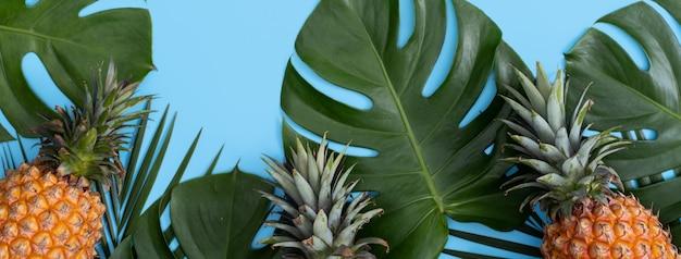 열 대 야자수와 몬스 테라 신선한 파인애플의 상위 뷰는 파란색 테이블 배경에 나뭇잎.