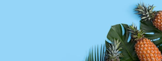 Вид сверху свежего ананаса с тропической пальмой и листьями монстеры на синем фоне таблицы.