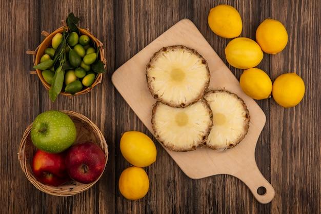 木製のキッチンボード上の新鮮なパイナップルの上面図バケツにキンカンと木製の壁に隔離されたレモンとバケツにカラフルなリンゴ