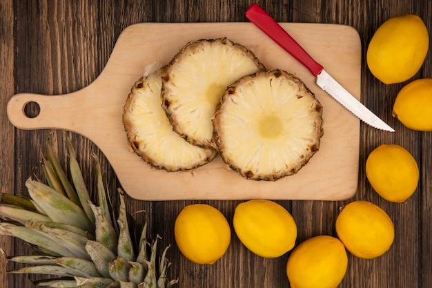 木製の壁に分離されたレモンとナイフと木製のキッチンボード上の新鮮なパイナップルの上面図