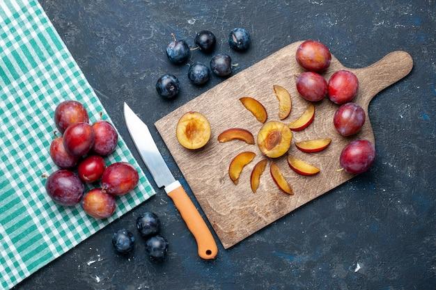 Вид сверху на свежие сливы, цельные и сочные, нарезанные на темном столе, фруктовое витаминное лето