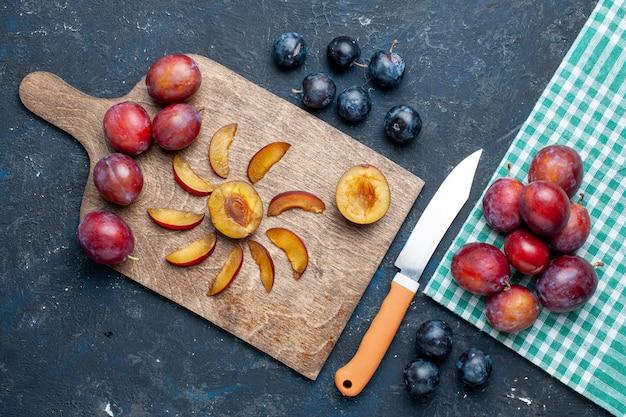 Вид сверху на свежие сливы, цельные, спелые и сочные, нарезанные на темных фруктовых свежих витаминах летом