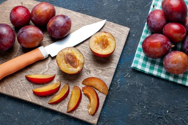 Вид сверху на свежие сливы, цельные и сочные, нарезанные на темно-сером столе, свежие фрукты, витамины, лето