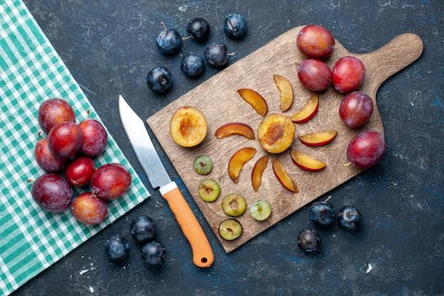 新鮮なプラムの上面図全体がまろやかでジューシーな灰色の暗い机の上でスライスされた、フルーツの新鮮なビタミンの夏
