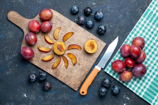 新鮮なプラム全体の平面図は、灰色がかった暗い机の上でまろやかでジューシーにスライスされ、フルーツの新鮮なビタミンの夏