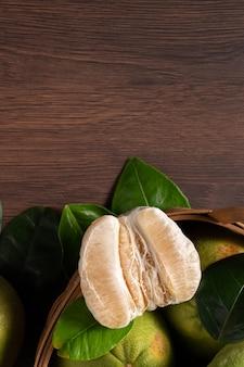 中秋節の果物の暗い木製のテーブルの背景に新鮮なザボンの上面図。