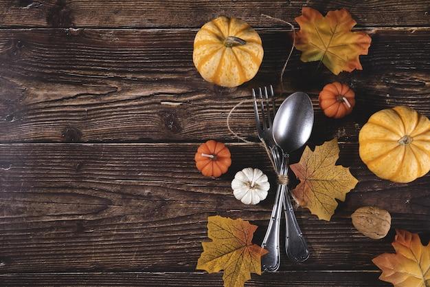 Вид сверху свежих тыкв, грецких орехов, осенних листьев с вилкой и ложкой на деревянном столе