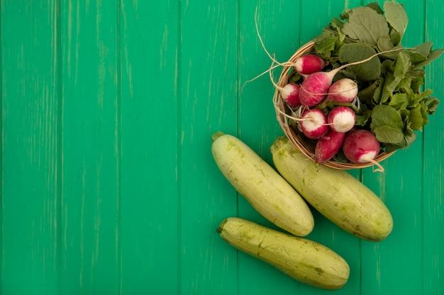 コピースペースのある緑の木製の壁に分離されたズッキーニとバケツの新鮮な大根の上面図