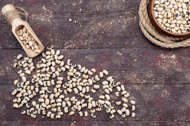 茶色の机全体に広がる新鮮な生豆の上面図、食品生豆ハリコット