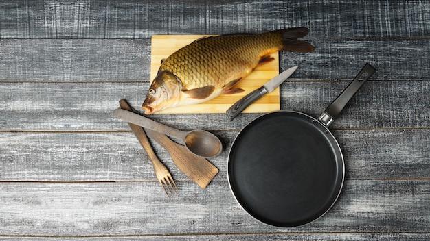 Вид сверху свежего сырого карпа на набор деревянных ложек и сковороды на разделочной доске на черном столе