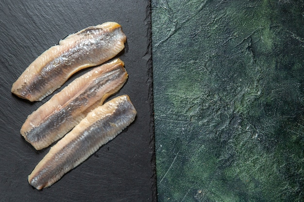 ミックスカラーの背景の右側にある黒い木製のまな板に新鮮な生のみじん切りの魚の上面図