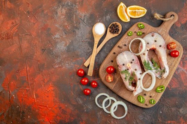 混合色の表面の左側にある木製のまな板に新鮮な生の魚とペッパーオニオングリーントマトの上面図