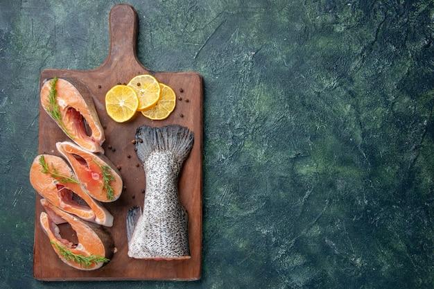 어두운 혼합 색상 테이블의 오른쪽에 나무 절단 보드에 신선한 생선 레몬 슬라이스 녹색 후추의 상위 뷰