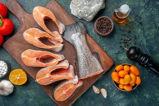 木製のまな板とスパイスオイルボトルレモンキンカンニンニクのダークミックスカラーテーブルの新鮮な生の魚の上面図