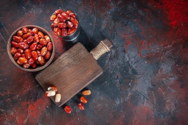 그릇에 있는 신선한 생 은베리 과일과 혼합 색상 배경의 나무 커팅 보드에 대한 상위 뷰