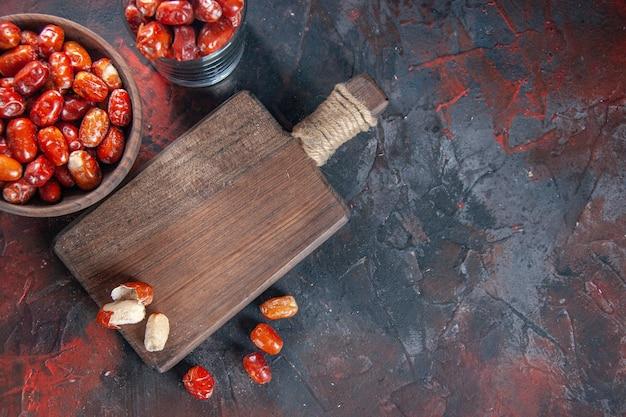 ボウルとミックスカラーの背景の右側にある木製のまな板に新鮮な生のグミの果実の上面図