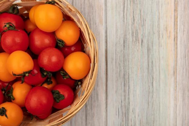 복사 공간 회색 나무 표면에 양동이에 신선한 붉은 색과 오렌지색 토마토의 상위 뷰