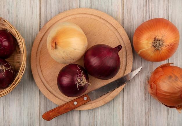 Вид сверху свежего красного и желтого лука на деревянной кухонной доске с ножом с желтым луком, изолированным на сером деревянном фоне