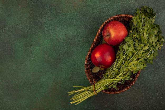 コピースペースのある緑の表面のバケツに新鮮な赤いリンゴとパセリの上面図