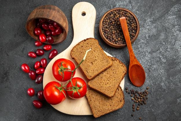 회색 표면에 빵 덩어리와 토마토와 신선한 빨간 층층 나무의 상위 뷰