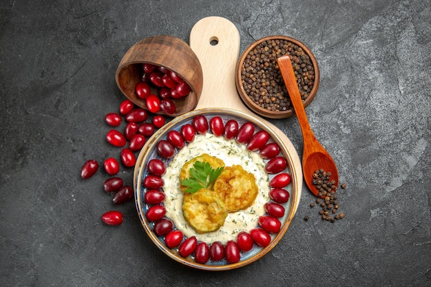 灰色の表面に調味料と調理されたカボチャと新鮮な赤いハナミズキの上面図