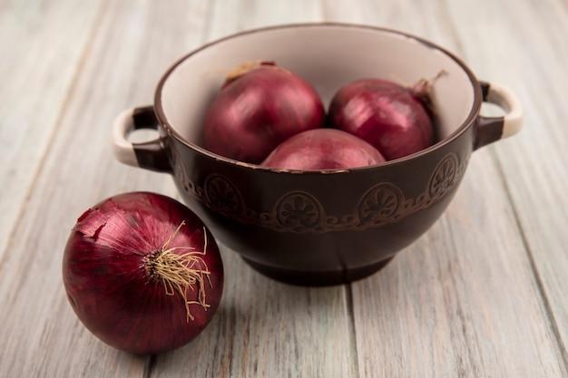 회색 나무 표면에 그릇에 신선한 붉은 양파의 상위 뷰