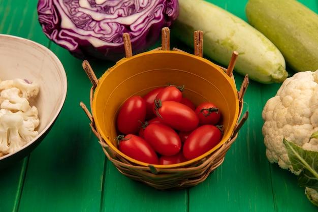 Вид сверху свежих красных сливовых помидоров на ведре с фиолетовой цветной капустой и сельдереем, изолированными на зеленой деревянной стене