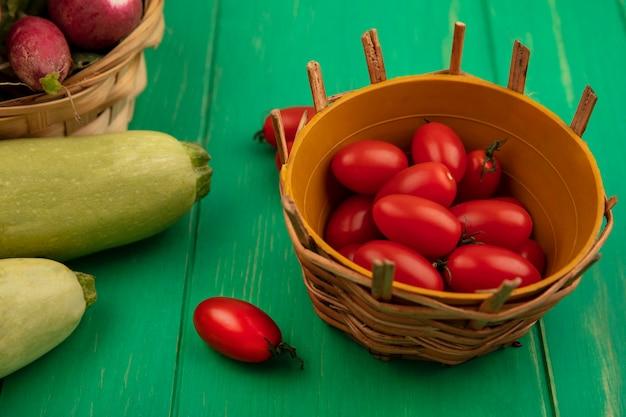 Вид сверху свежих красных сливовых помидоров на ведре с редисом на ведре с цукини, изолированным на зеленой деревянной стене