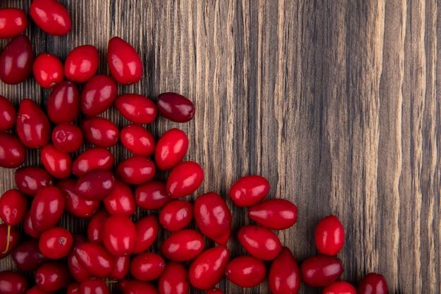 コピースペースと木製の背景に分離された新鮮な赤い熟したコーネルベリーの上面図