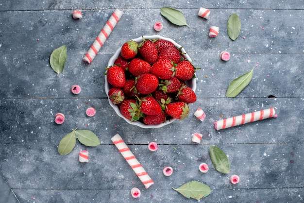スティックキャンディーと灰色のフルーツベリーフレッシュキャンディースイートの緑の葉と一緒にプレート内の新鮮な赤いイチゴの上面図