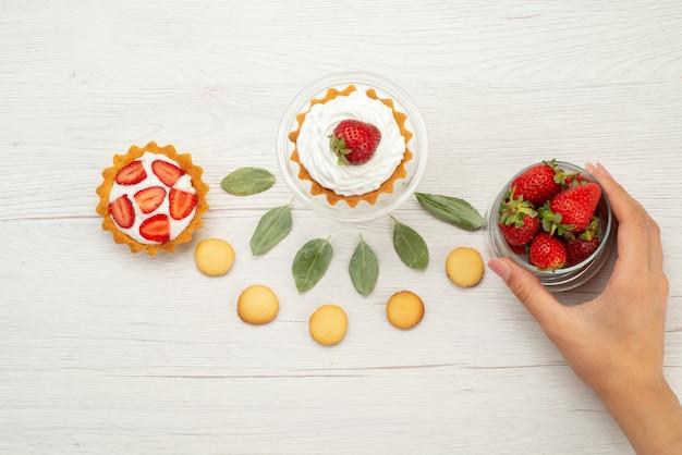 新鮮な赤いイチゴの上面図まろやかでおいしいベリーとケーキとクッキーライトグレーの机の上、フルーツベリーレッドフレッシュ