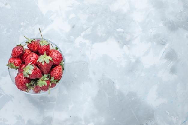 Вид сверху свежих красных ягод клубники, спелых летних ягод внутри стеклянной тарелки на свету, ягодных фруктов, мягких витаминов