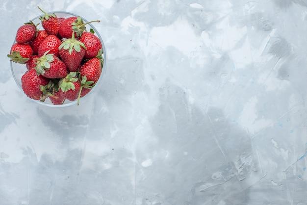 Вид сверху свежей красной клубники, спелых летних ягод внутри стеклянной тарелки на светлом столе, ягодный фруктовый мягкий витамин