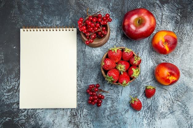 Вид сверху свежей красной клубники с персиками и яблоком на темной поверхности