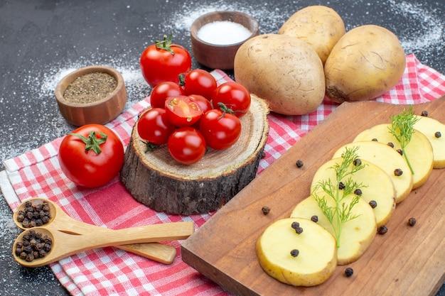 黒と白のミックスカラーの背景にストリップタオルで新鮮な赤いトマトと全体の刻んだジャガイモのスパイスの上面図