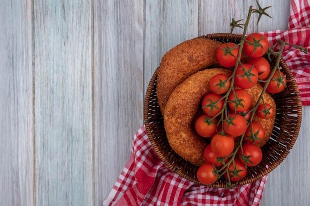 コピースペースと灰色の木製の背景の上の袋布にベーグルとバケツの上の新鮮な赤いトマトの上面図