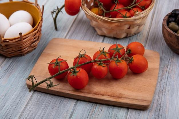 灰色の木製の背景に有機卵とオリーブとバケツにつるトマトと木製のキッチンボード上の新鮮な赤いトマトの上面図