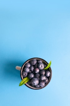 Вид сверху свежих спелых ягод черники с мятой в металлической кружке на синей поверхности