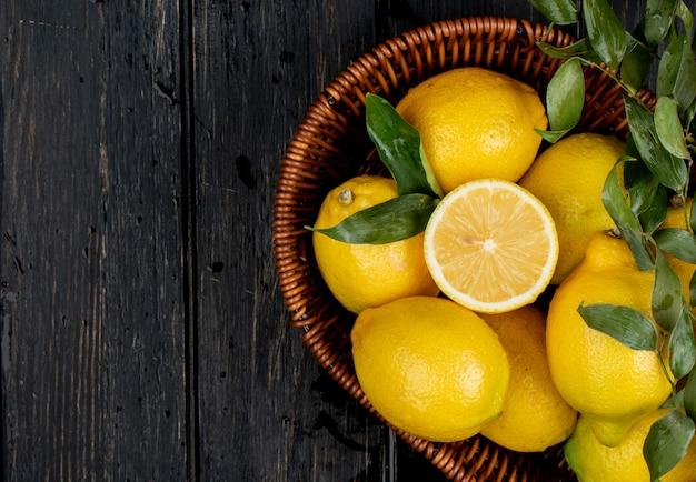 Вид сверху свежих спелых лимонов в плетеной корзине на черном с копией пространства