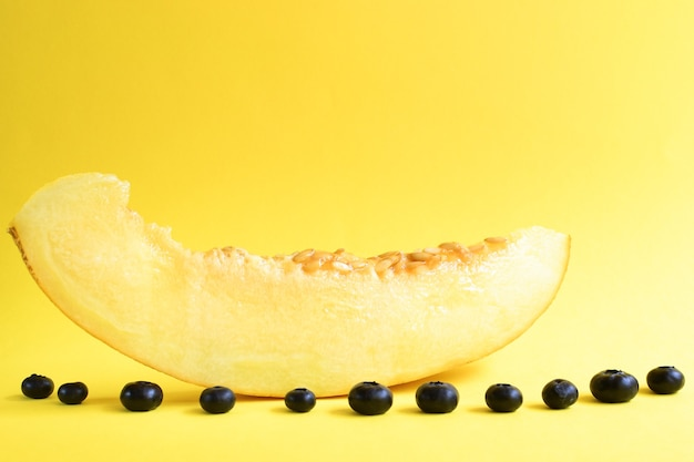 黄色の背景に新鮮な熟したメロンの上面図。メロンとブルーベリー。最小限の食品の概念。クリエイティブな料理。
