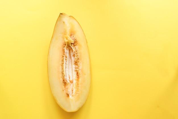 黄色の背景に新鮮な熟したメロンの上面図。最小限の食品の概念。クリエイティブな料理。黄色で分離