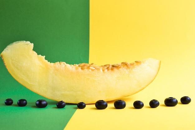 黄緑色の背景に新鮮な熟したメロンの上面図。メロンとブルーベリー。最小限の食品の概念。クリエイティブな料理。