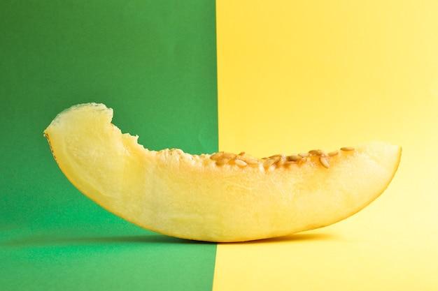 黄緑色の背景に新鮮な熟したメロンの上面図。最小限の食品の概念。クリエイティブな料理。