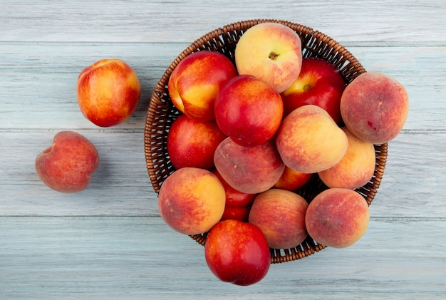 白い背景の枝編み細工品バスケットで新鮮な熟したネクタリンと桃のトップビュー